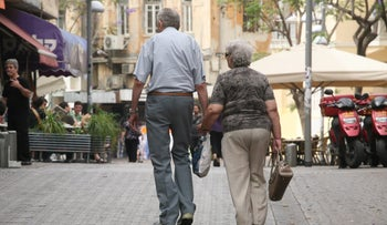 An illustrative photo shows an elderly couple strolling in Tel Aviv.