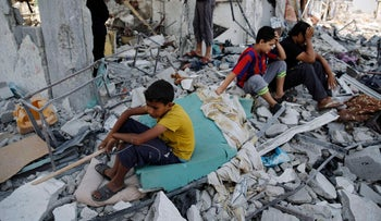 Palestinians sit on the remains of their destroyed homes after returning to Beit Hanoun, Gaza, August 5, 2014.