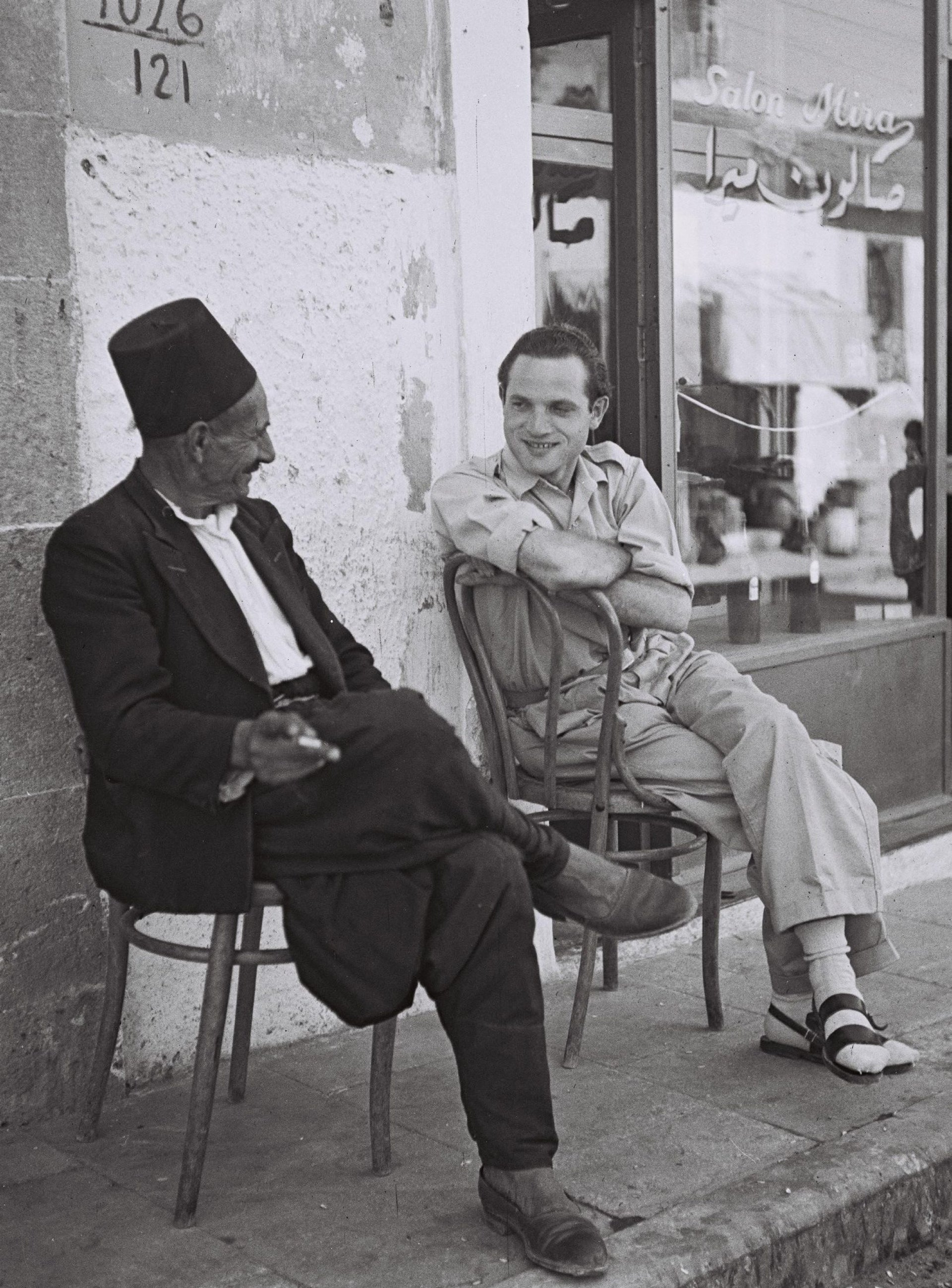 An immigrant from Bulgaria chatting with an Arab man in Jaffa, 1949.