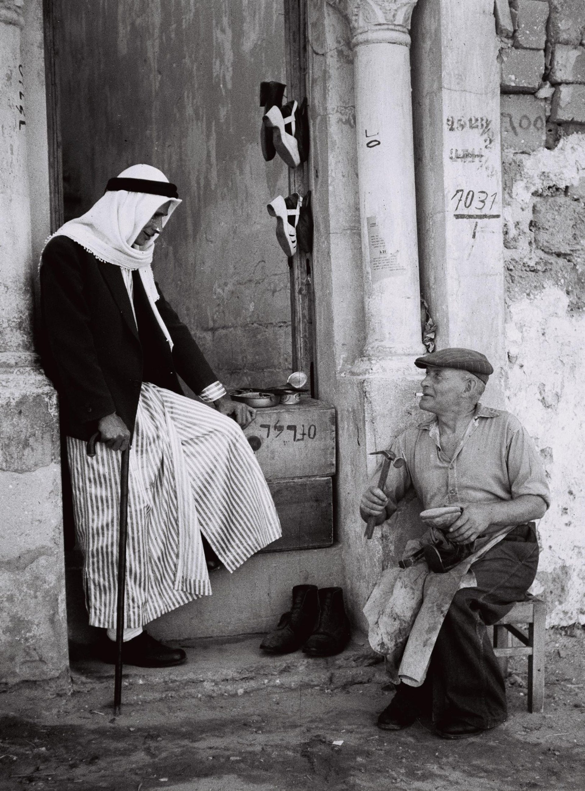 A Bulgarian cobbler who recently immigrated to Israel, speaking with an Arab man in Jaffa, 1949.