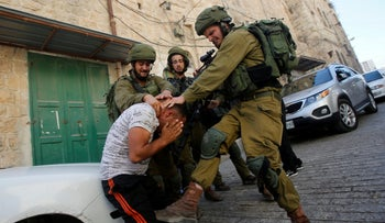 Israeli soldiers detain a Palestinian during a searching raid by Israeli troops, in the West Bank city of Hebron September 20, 2016.