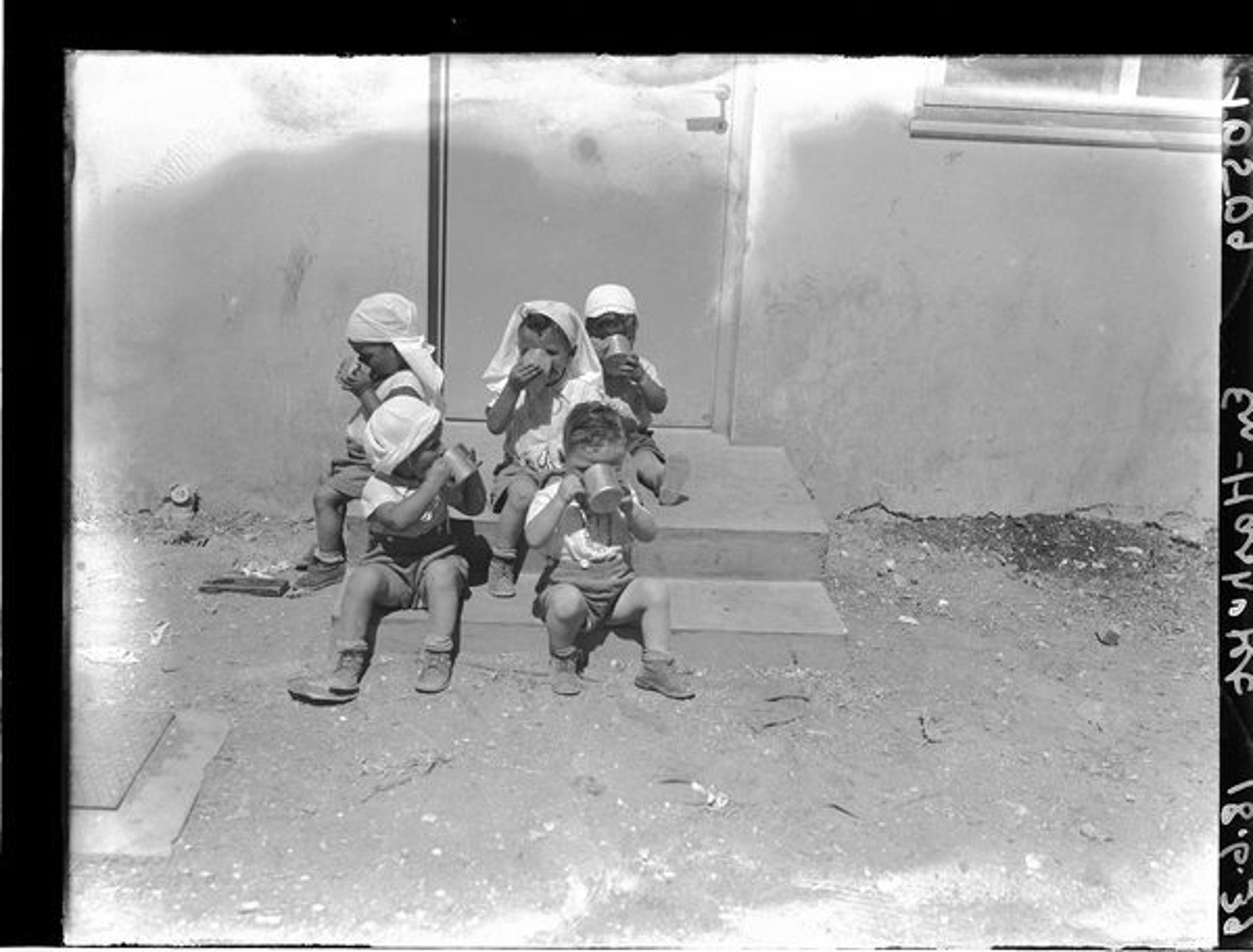 A group of children sitting on steps and drinking from mugs, Kibbutz Ein Hashofet, 1939