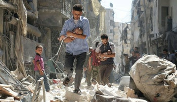 Syrian men carrying babies make their way through the rubble of destroyed buildings following a reported airstrike in Aleppo on September 11, 2016.