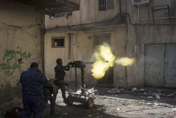 Federal policemen fire towards Islamic State positions in the old city during fighting on the western side of Mosul, Iraq, Thursday, March 30, 2017.