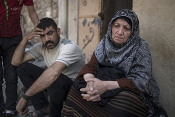 Widad Ibrahim, right, sits outside her house near the old city during fighting between Iraqi security forces and Islamic State militants on the western side of Mosul, Iraq, Thursday, March 30, 2017.