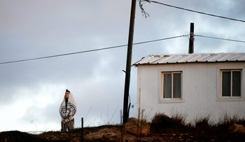 FILE PHOTO: An Israeli man wearing a Jewish prayer shawl, prays near a home in the early morning, in the Jewish settler outpost of Amona in the West Bank December 15, 2016.
