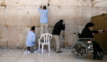 Men clear notes placed in the cracks of the Western Wall, Judaism's holiest prayer site, to clear space for new notes ahead of the Jewish holiday of Passover, in Jerusalem's Old City March 29, 2017.