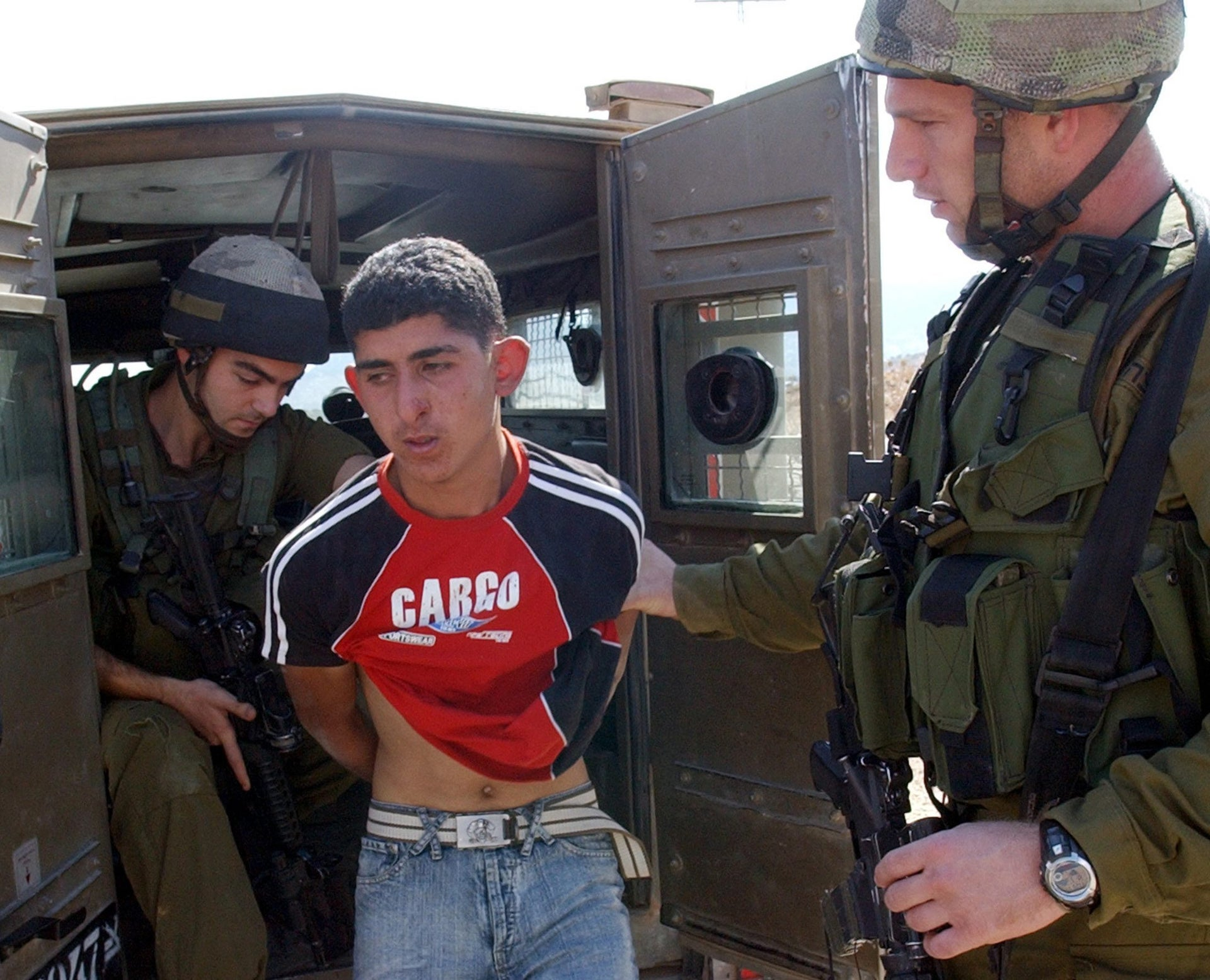 FILE PHOTO: Israeli soldiers arrest a Palestinian teenager at the Beit Furik checkpoint near the West Bank city of Nablus October 5, 2005.