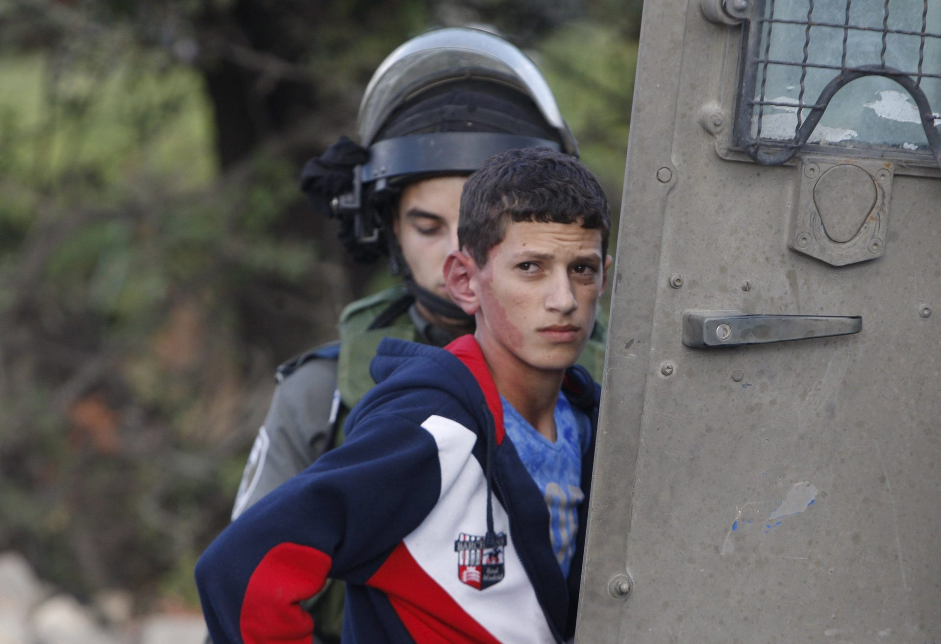 A Border Policeman detaining a Palestinian youth near Hebron in 2015.
