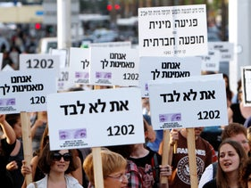 FILE PHOTO: 'You're not alone' signs in solitary of sexual assault victims at protest against Israel's shamed former President Moshe Katzav, convicted of rape.