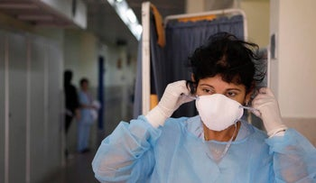 FILE PHOTO: An Israeli nurse who did not identify herself adjusts a protective mask as she stands outside the room of a swine flu patient at Meir Hospital in Kfar Saba, Israel, Thursday, April 30, 2009.