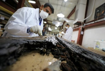 An Egyptian scientist works on restoring a piece of the second Khufu boat at a temporary laboratory set up next to the Great Pyramids where it was discovered, in Giza, Egypt March 29, 2017