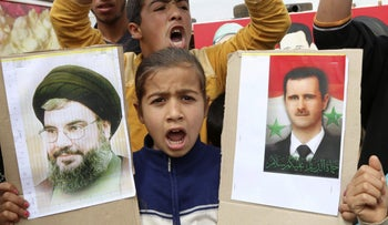 A Syrian refugee girl shout slogans as she holds pictures of Syria's President Bashar Assad (R) and Lebanon's Hezbollah leader Sayyed Hassan Nasrallah.