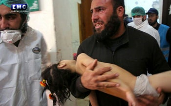 A man carries a wounded child following a suspected chemical attack, northern Idlib province, Syria, April 4, 2017.