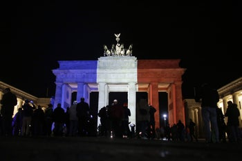 People gather in front of the Brandenburg Gate illuminated in the French national colors for the victims killed in the Friday's attacks in Paris, France, in Berlin, Saturday, Nov. 14, 2015.