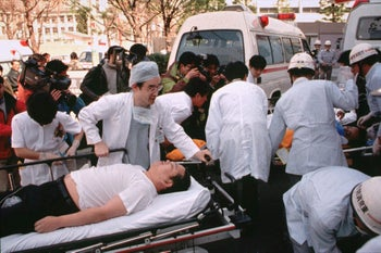 FILE - Subway passengers affected by sarin gas planted in central Tokyo subways are carried into St. Luke's International Hospital in Tokyo in March 1995.