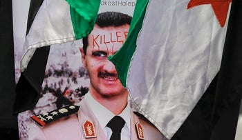 A poster of Syrian President Bashar Assad at a protest outside Syria's embassy in Bucharest, Romania, March 17, 2017.