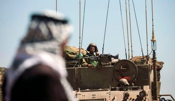 Israeli soldiers drive military vehicles past a Palestinian man during a military exercise near the West Bank village of Aqraba, east of Nablus, on April 4, 2017.