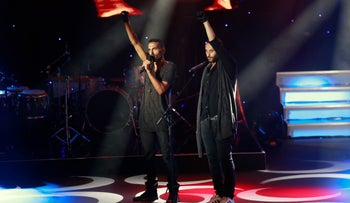"""Jewish performer Yossi Zabari and Tamer Nafar, the Arab star of the Israeli film """"Junction 48,"""" raise their fist in a sign of protest during Ophir Awards. September 22, 2016."""