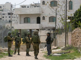 Israeli soldiers quizzing Palestinians in Hebron