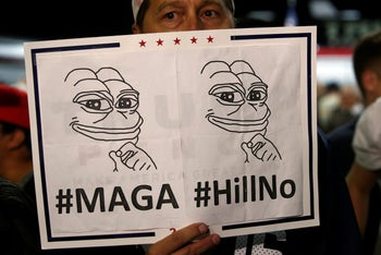 A man hides his face behind a Pepe the Frog sign - an icon of the alt-right - after Republican a Donald Trump rally in New Mexico, U.S. October 30, 2016.