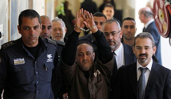 An Israeli prison guard escorts jailed Fatah leader Marwan Barghouti, center,  to a deliberation at Jerusalem Magistrate's Court in January, 2012.