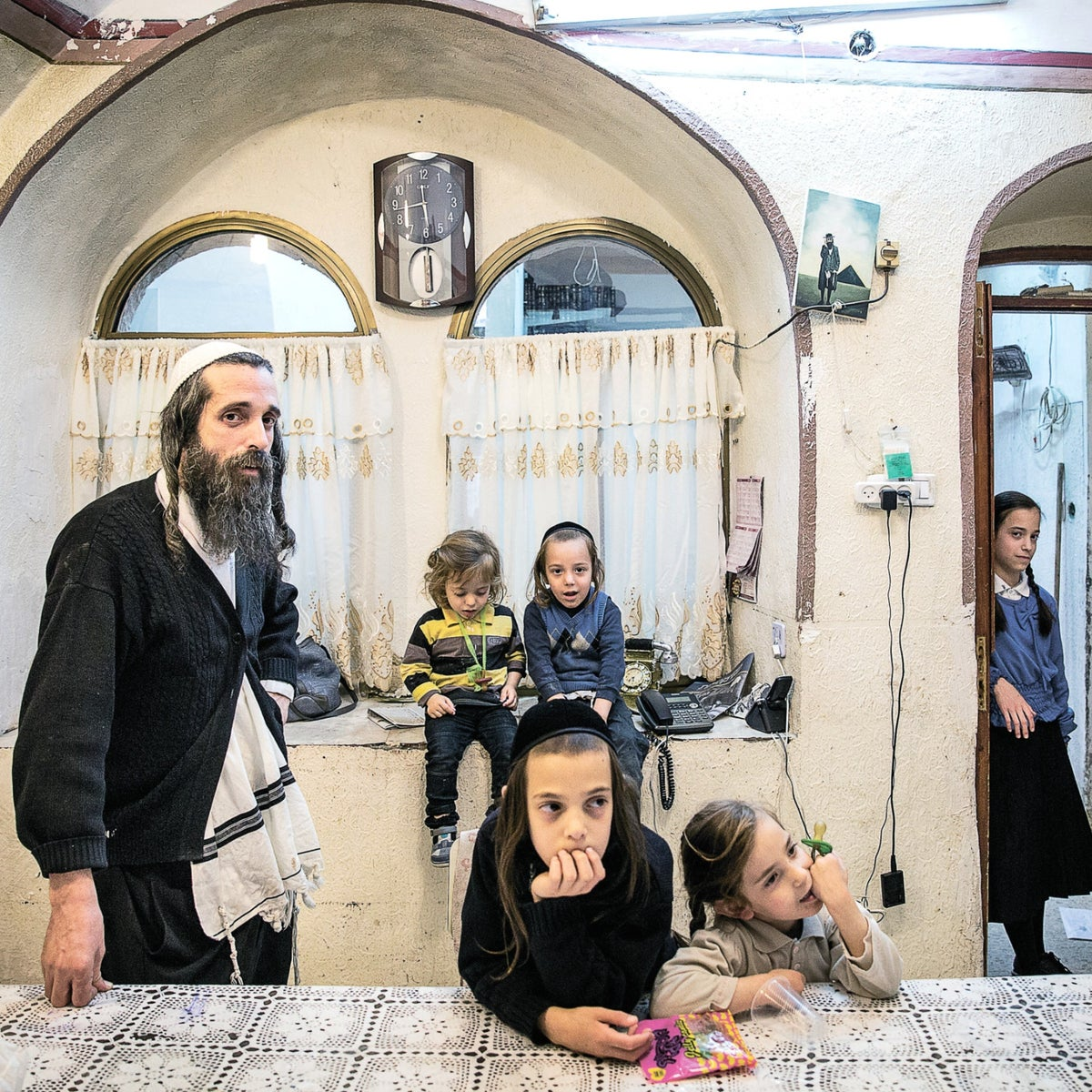 Yoelish Kraus with some of his 16 children at home in Jerusalem.  'He is like the king of the family,' says his wife.