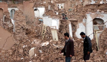 File photo: People walk past houses damaged by an earthquake in northeast Iran.