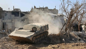 Syrian pro-government forces manoeuver an armored vehicle as they advance through Qabun district on May 13, 2017.