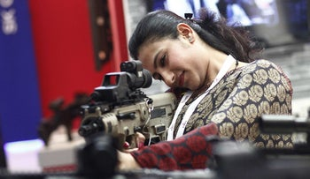 A visitor holds an Israeli-made rifle during the 8th International Land and Naval Defense system exhibition, in New Delhi, India, on February 6, 2014.