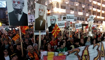 """Protesters carry posters of George Soros and banners reading """"No for Soros Government"""", as they march through a street in Skopje, Macedonia, March 20, 2017."""
