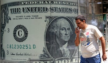 A man walking past a currency exchange bureau advertisement showing images of the U.S dollar and other currencies in Cairo, August 3, 2016.