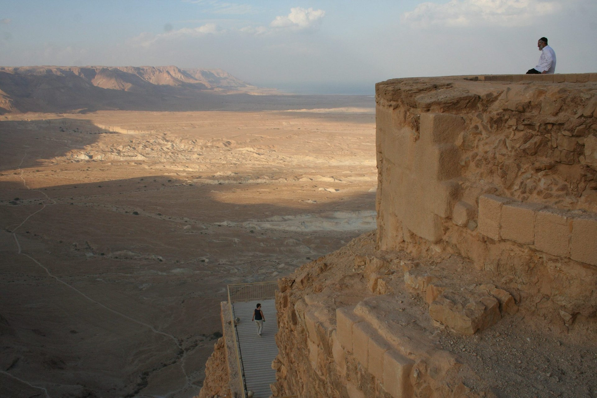 Masada: The view of the surrounding desert from the top. Picture shows a man sitting on the top of the walls looking out over the desert sprawling at the feet of the plateau.