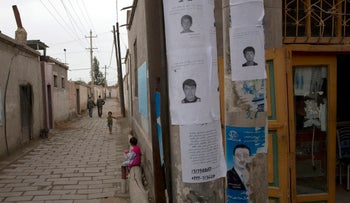 Wanted posters of men involved in terror attacks posted on a street of Aksu in western China's Xinjiang province in 2014.