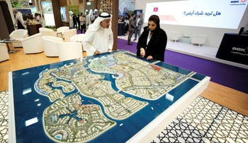 Visitors look at the mockup of a project at the Gulf Property, Construction and Interior Exhibition in Manama, Bahrain April 26, 2017. REUTERS/