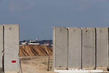 The separation fence: We see the cement blocks of the fence, between which a town peeps.