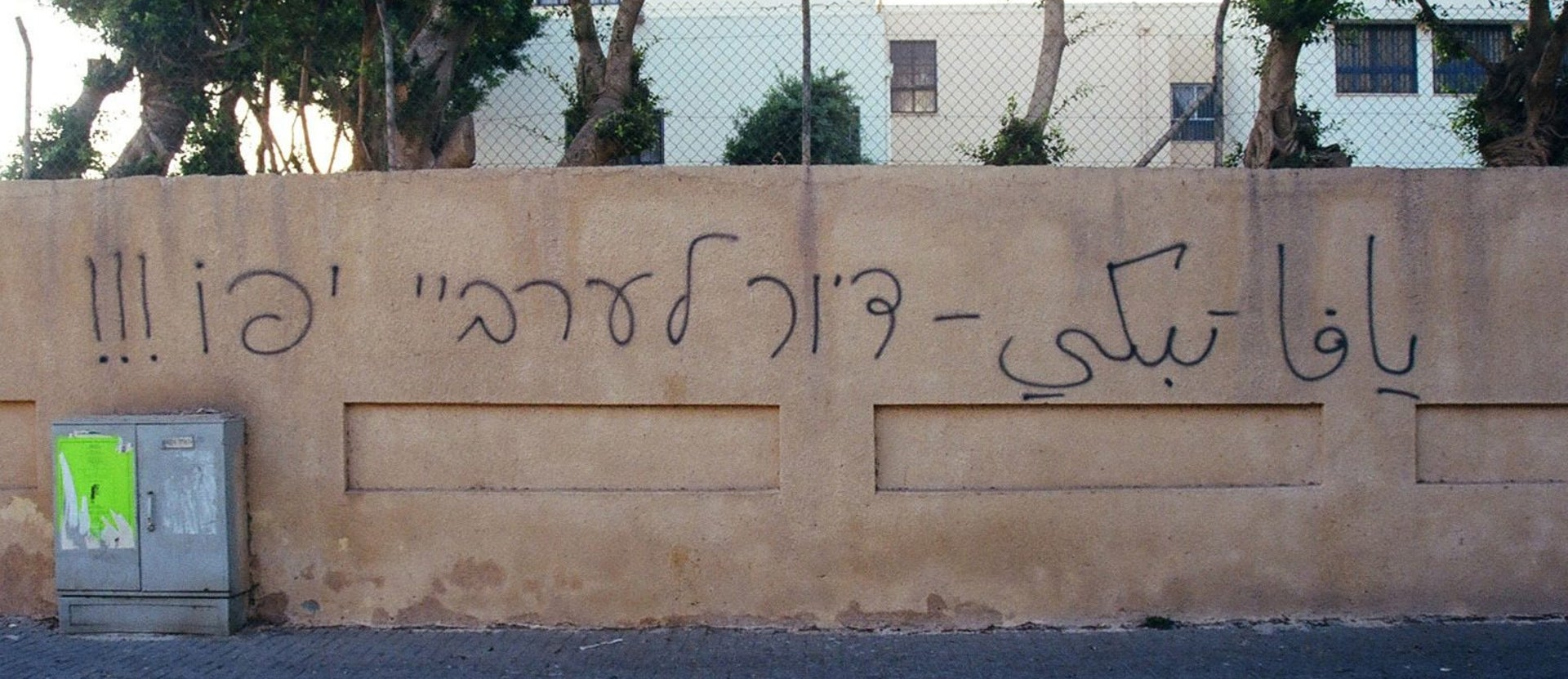 "In Arabic: ""Jaffa is crying."" In Hebrew: ""Housing for Jaffa's Arabs."""