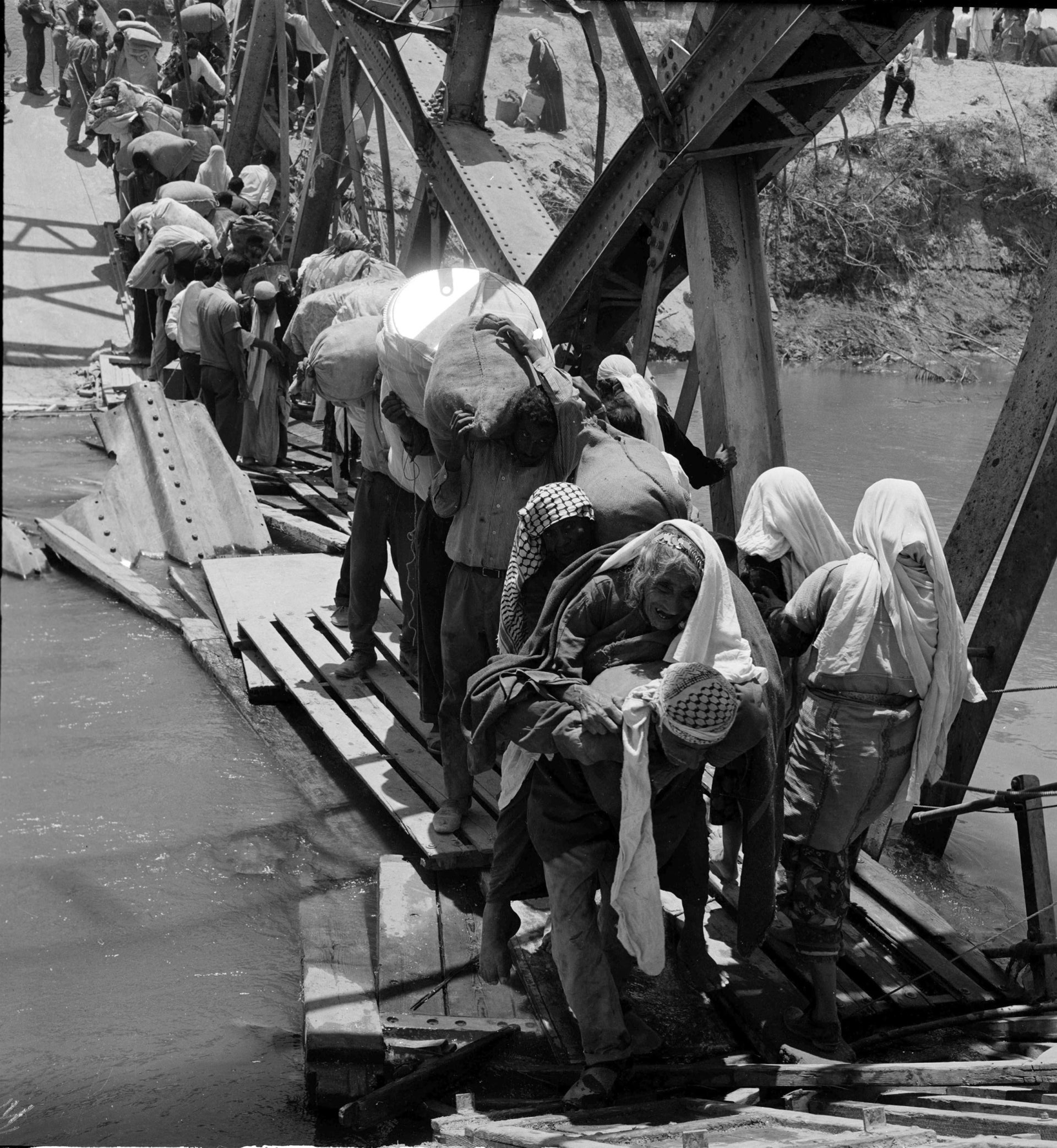 "In this 1967 photo from the U.N. Relief and Works Agency, UNRWA, archive, Palestine refugees flee across over the Jordan river on the damaged Allenby Bridge during the 1967 Arab-Israeli war.  The photo is part of UNWRA's vast photo archive being digitized in Gaza and Denmark to preserve a record of one of the world's most entrenched refugee problems, created in what the Palestinians call the ""Nakba,"" or ""catastrophe""-- their uprooting in the war over Israel's 1948 creation."