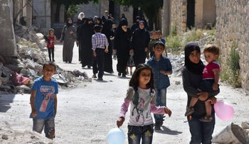 Syrians walk in a street after attending a war safety awareness class at a UNICEF make-shift school in Aleppo, on May 18, 2017.