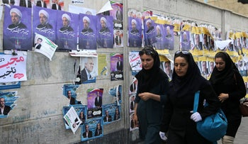 Iranians walk by a wall plastered with election posters backing President Hassan Rohani in Tehran, May 18, 2017.
