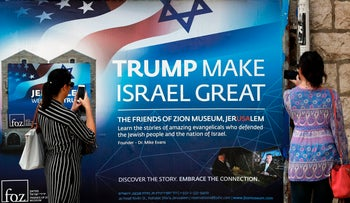 Two women take a picture of a poster welcoming and supporting US President Donald Trump in downtown Jerusalem, on May 19, 2017, three days ahead of a two day official visit of US President Donald Trump in Israel and the Palestinian territories.