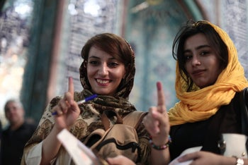 Iranian women show their ink-stained fingers after voting for the presidential elections at a polling station in Tehran on May 19, 2017.