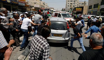Palestinians attack a passing vehicle belonging to an Israeli settler near the Hawara checkpoint, near the West Bank city of Nablus May 18, 2017.