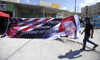 Palestinian men hold a banner bearing a portrait of US President Donald Trump (L) and Palestinian president Mahmud Abbas (R) at a printer's in the West Bank town of Bethlehem, on May 21, 2017, ahead of a two day official visit of Trump in Israel and the Palestinian territories. / AFP PHOTO / Musa AL SHAER