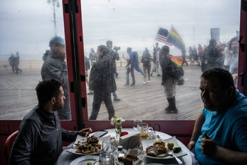 Patrons of a Russian restaurant in Brighton Beach watch the Russian-speaking LGBT pride parade on the boardwalk, Brooklyn, May 20, 2017.
