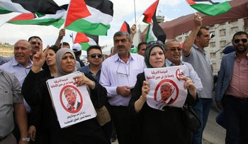Palestinian protesters hold placards against Trump while they demonstrate in support of prisoners in Israeli jails at Hawara checkpoint in the West Bank, May 23, 2017.