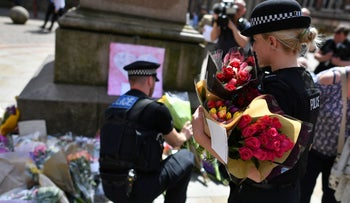 Police officers lay floral tributes in St Ann's Square in Manchester left in commemoration to those killed and injured in the Manchester Arena on Monday, May 23, 2017.