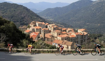 Cyclists ride past the village of Sainte Lucie de Tallano during the International Criterium cycling race on Corsica March 25, 2012.