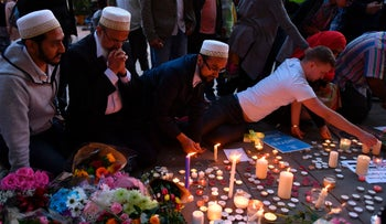 People pray and light candles set up in front of floral tributes in Albert Square in Manchester, northwest England on May 23, 2017.