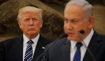 Israeli Prime Minister Benjamin Netanyahu talks on a podium as U.S. President Donald Trump listens during a ceremony commemorating the six million Jews killed by the Nazis in the Holocaust, in the Hall of Remembrance at Yad Vashem Holocaust memorial in Jerusalem May 23, 2017.